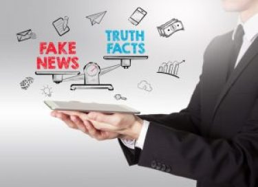 Fake News Infomation concept. Young man holding a tablet computer.