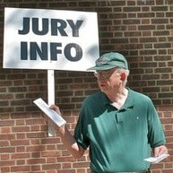"Man standing in front of a sign that says ""jury info"""