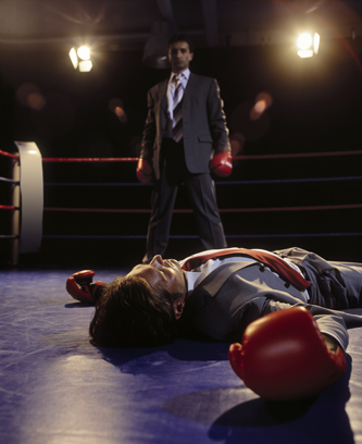 Two men in business suits in boxing ring, one unconscious on the mat, one standing. Illustrating article by Richard Klass about ejectment of a boxing gym.