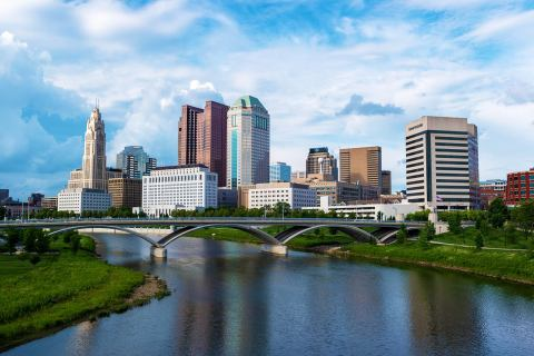 The skyline of downtown Columbus Ohio with bridge and water stretching in front