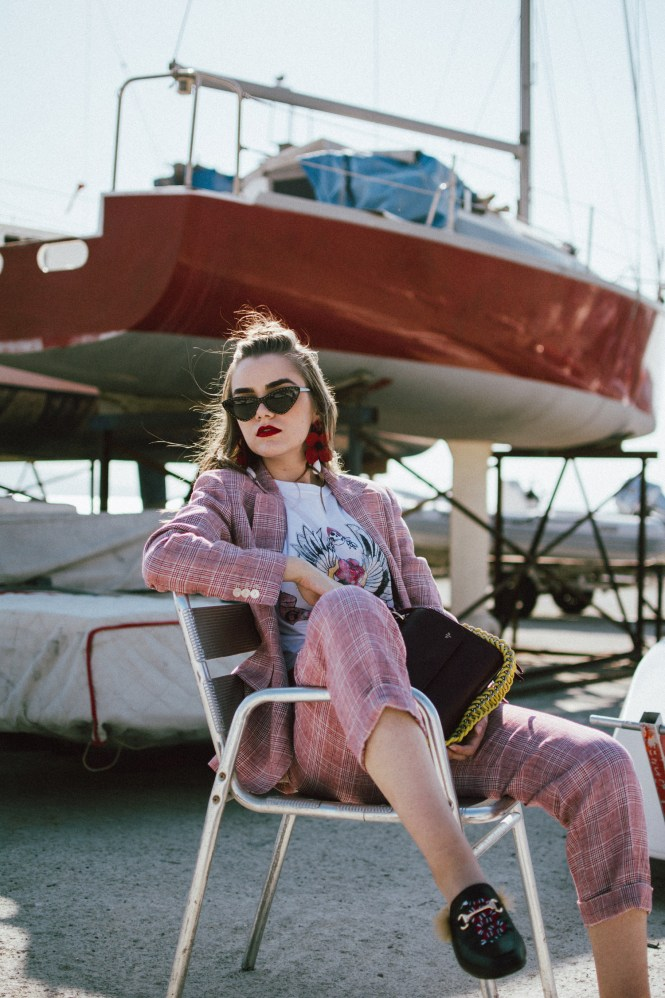 Massimo Dutti suit, graphic t-shirt, gucci inspired mules, graphic tees, lady bag, andreea birsan in izmir turkey, couturezilla, cute fall outfit ideas 2018, plaid linen suit, dressed in dutti, blush pink plaid suit, what shoes to wear with a women's suit, pointy cat eye sunglasses, tips on how to style a suit for women, the suit you need to wear this autumn, check printed blush pink double breasted blazer, blazers for women, the blazer you will wear on repeat this fall, how to style straight leg trousers, blush pink check printed linen trousers, how to wear linen in fall, check printed suit and gucci inspired fur mules, black mules with fur, the high street alternative to the popular gucci mules, gucci dupe mules, black loafers, gucci dupe loafers, isla fontaine dark red lady bag, italian leather bag, genuine leather bag, burgundy bag and pink suit, graphic t-shirt and suit, printed t-shirt, guns and roses t-shirt, white tee, graphic t-shirt, printed, pink plaid suit, where to get a pink plaid suit, gucci inspired black loafers with lion embroidery and fur, gucci princeton inspired, classic shoes, timeless shoes and pink plaid suit, pink plaid suit and guns and roses t-shirt, rock band t-shirt, rock tee, zara big flower earrings, moschino pointy cat eye sunglasses, cat eye sunnies, embellished sunglasses, where to find the best cat eye sunglasses, what to wear in turkey in autumn, how to look Parisian chic, European summer street style inspiration for women 2017, pinterest chic outfit ideas for woman, summer outfit ideas, summer ootd inspiration, outfit of the day, ootd, fashion icon, style inspiration, fashionista, fashion inspiration, style inspo, what to wear in summer, how to look French, chic on a budget, zara outfit, mango, topshop, asos, river island, forever 21, urban outfitters, how to mix high end pieces with luxury ones, zara and Gucci,outfit alternatives for summer, tomboy chic, minimal outfit, tumblr girls photos, pictures, happy girl, women, smart cas