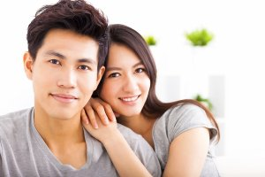 Young happy asian couple hugging and smiling