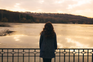 A woman overlooking a lake and thinking about her alcohol use.
