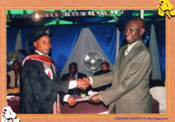 Boachie presenting a certificate to the graduate