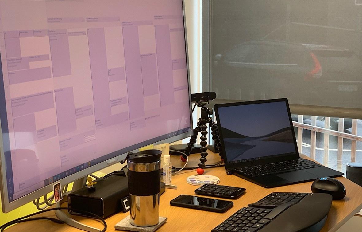 Bild på skrivbord med webbkamera, kaffekopp, dator och skärm.