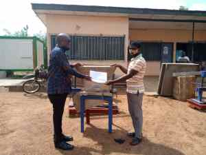 Emmanuel Louis Agama, South Tongu DCE presenting machine to beneficiary