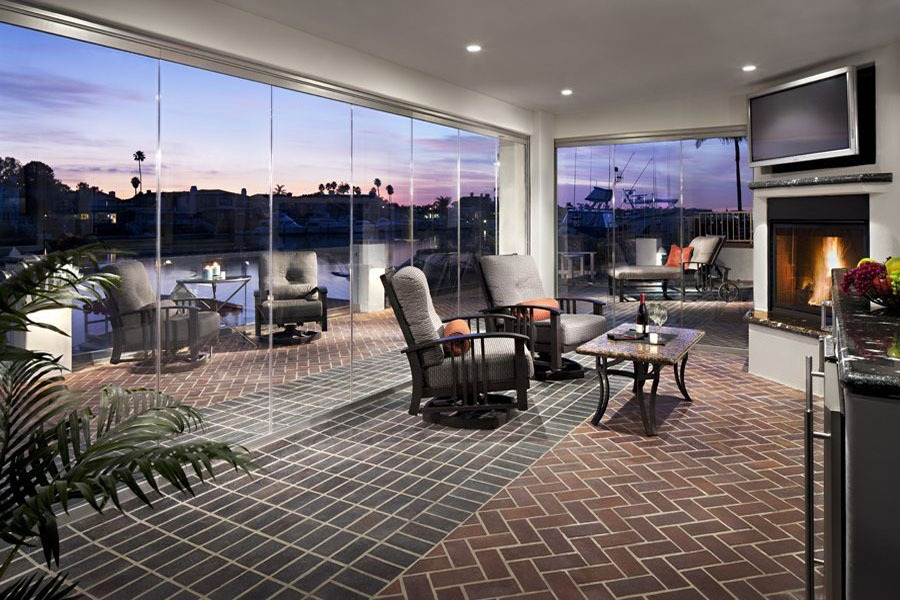 Looking at living room and patio with enclosed frameless sliding glass doors.
