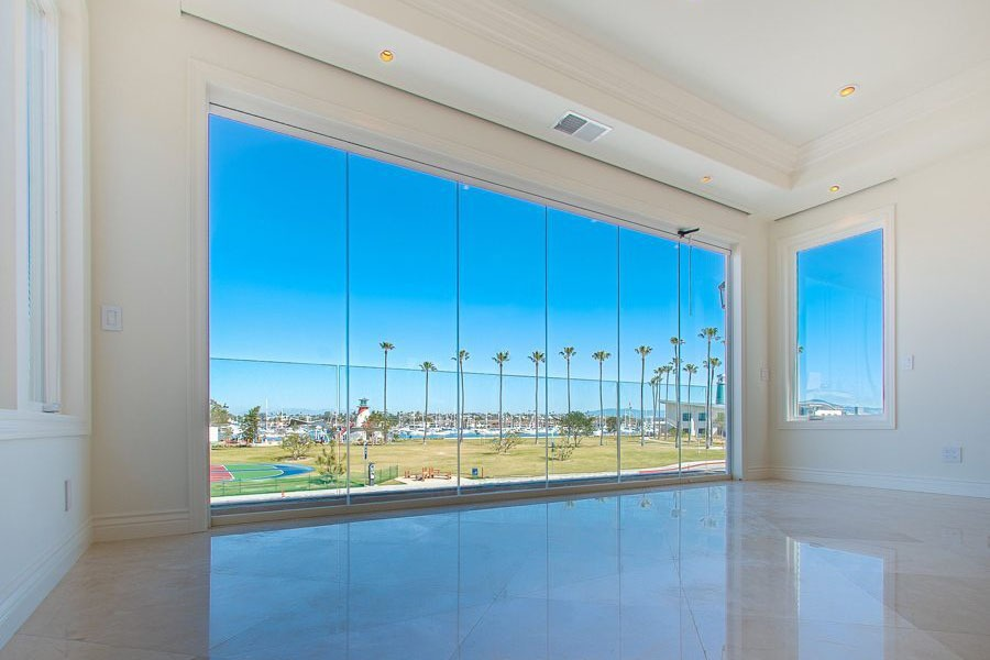 Looking from empty living room into bay with enclosed frameless sliding glass doors.