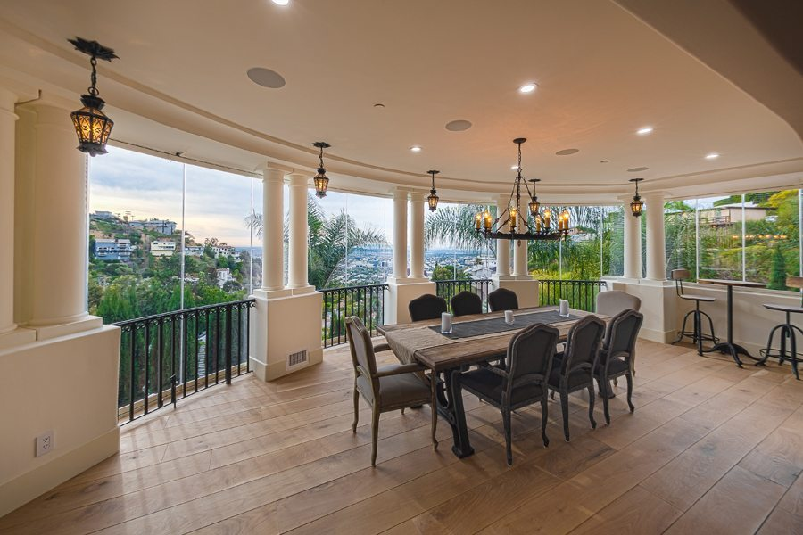 Enclosed frameless sliding glass door dining room patio with view of hill.
