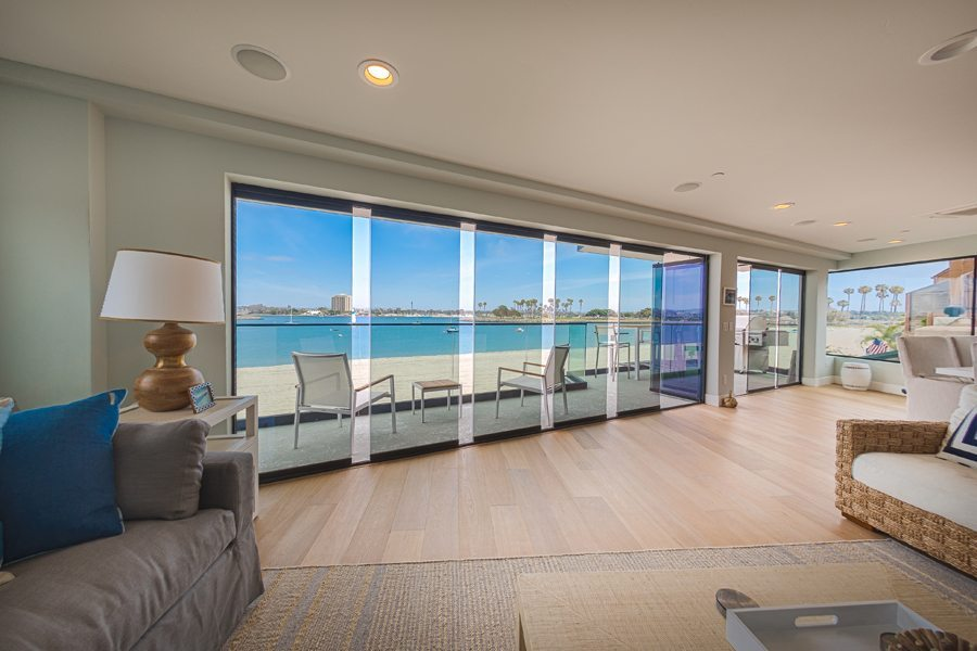 Looking from living and dining room out to patio with an staggered frameless sliding glass doors.