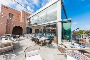 Restaurant patio dining area with enclosed frameless sliding glass doors.