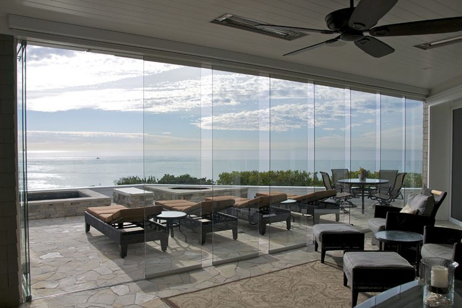 Staggered frameless sliding glass door with view of patio and ocean.
