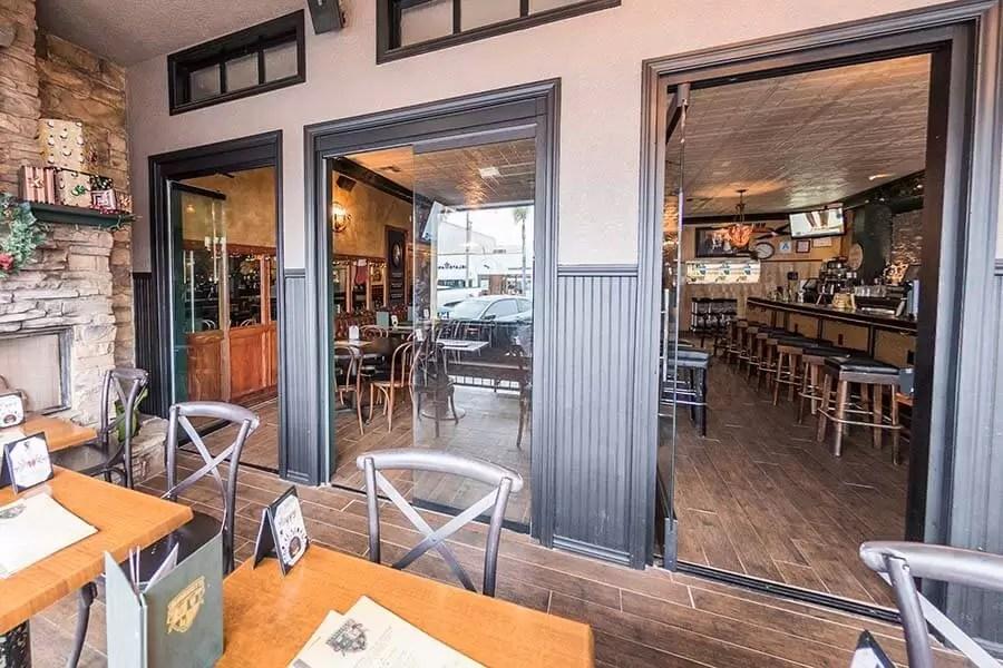 Restaurant tables with opened frameless sliding glass doors.
