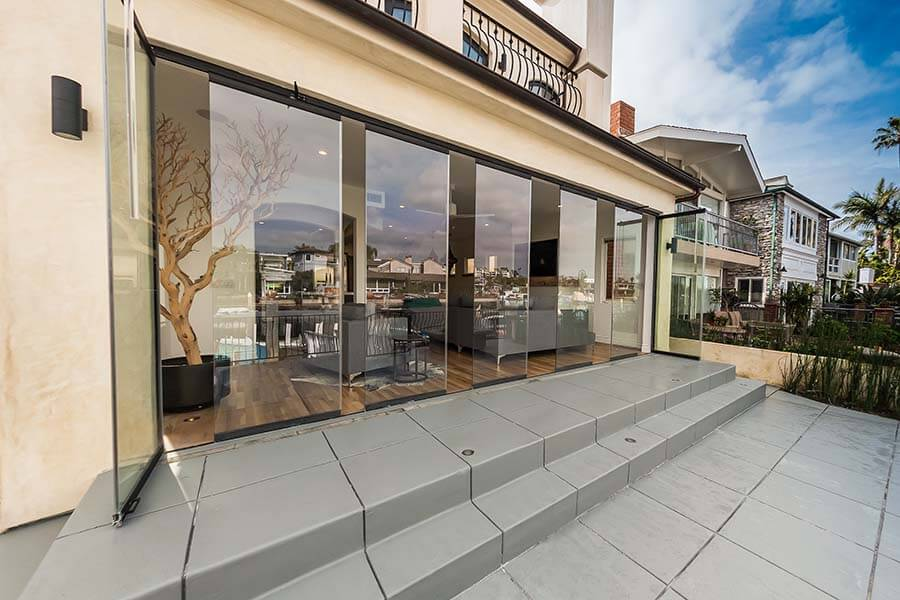 Partially open frameless sliding glass doors connecting living room with patio.