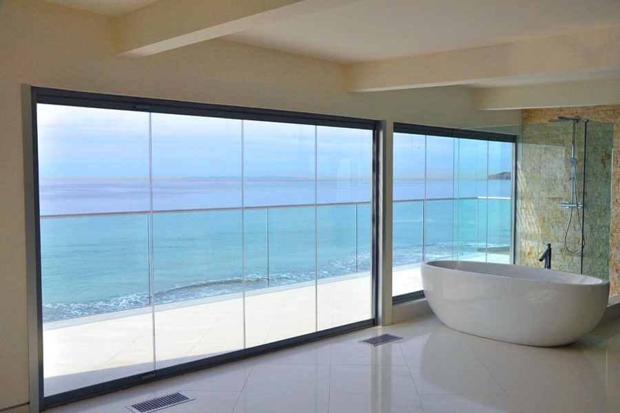 Bath tub with enclosed frameless sliding glass doors and windows.