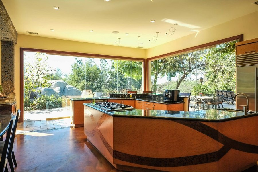 Open concept dining area and kitchen with closed frameless sliding glass doors showing the outdoors.