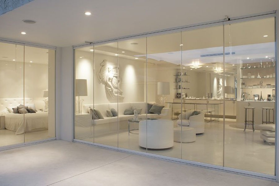 Enclosed frameless sliding glass doors looking into living room and bedroom.