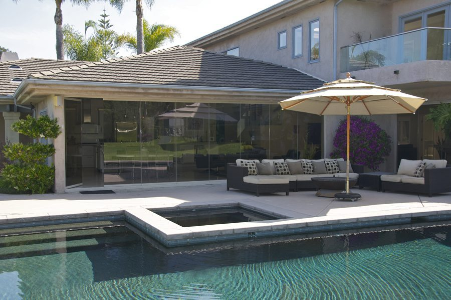 Pool and patio with enclosed frameless glass sliding doors and an open panel.