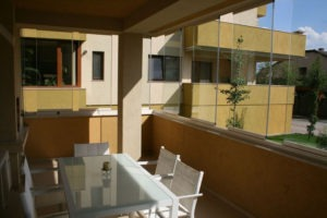Apartment patio with staggered frameless sliding glass windows.