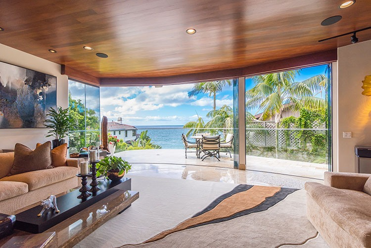 Looking outside from living room through open frameless glass doors