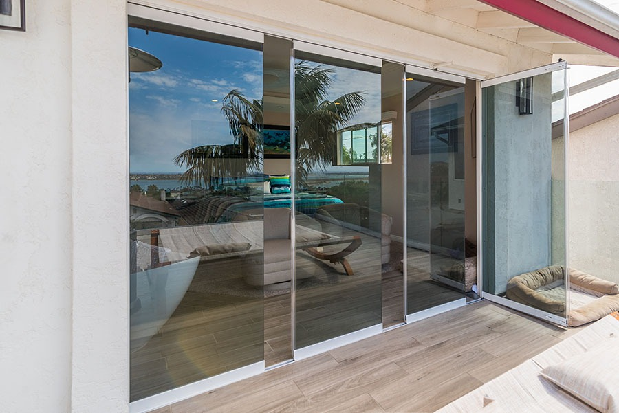 Patio and staggered frameless sliding glass door with one door frame swung open.