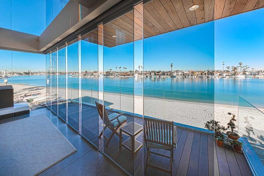 Staggered frameless sliding glass doors with view of patio and bay.