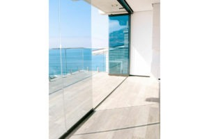 Half enclosed, half- stacked frameless sliding glass doors with patio and ocean view.
