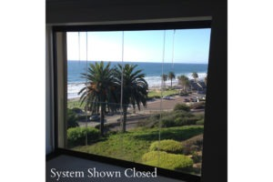 View of ocean and beach from frameless glass windows.