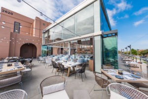 Restaurant patio tables with staggered frameless sliding glass doors.