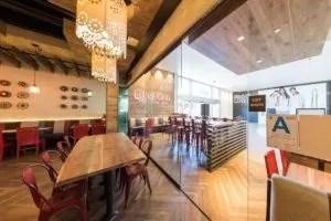Enclosed frameless sliding glass doors inside restaurant next to table.