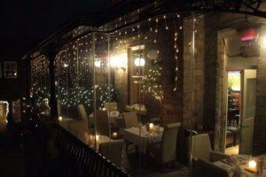 Enclosed restaurant patio with frameless sliding glass doors.