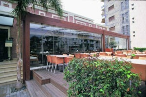 Patio tables next to enclosed frameless sliding glass doors in restaurant.