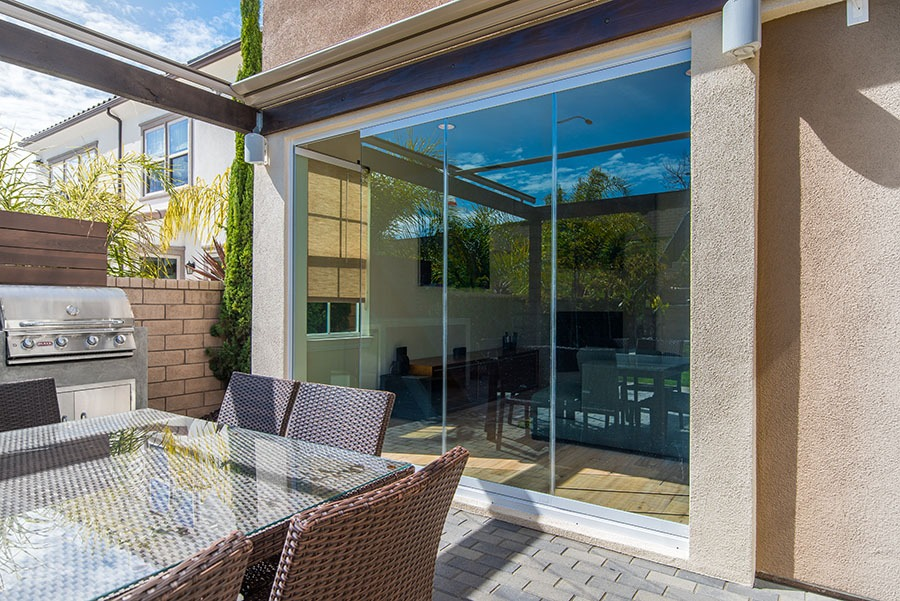 Looking from patio into living room with enclosed frameless sliding glass doors.