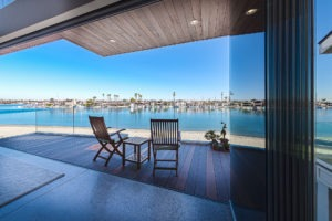 Stacked frameless sliding glass doors with patio and view of bay.