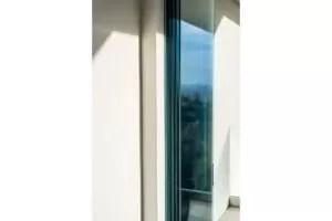 Frameless glass sliding door stacked next to doorframe.