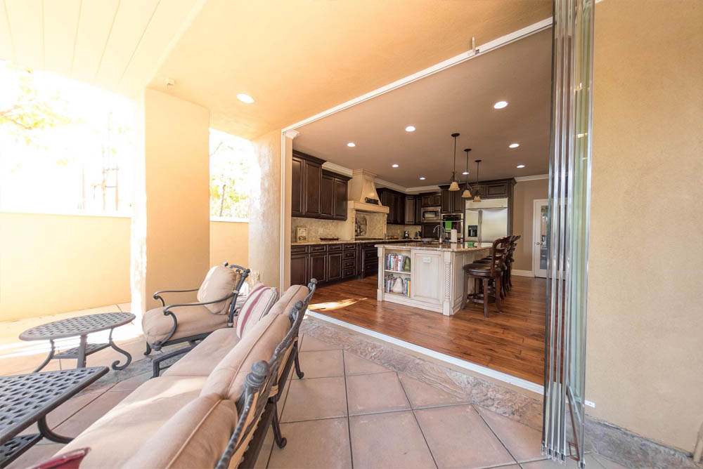 Looking into kitchen from patio with open frameless glass doors