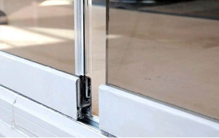Closeup of frameless glass door track