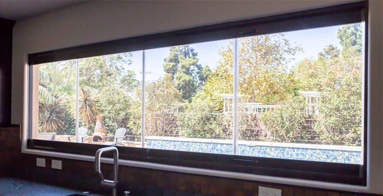 Looking out frameless glass windows from the kitchen.