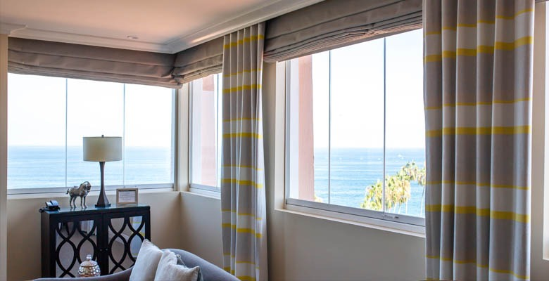 Framless glass windows in a living room overlooking the ocean.