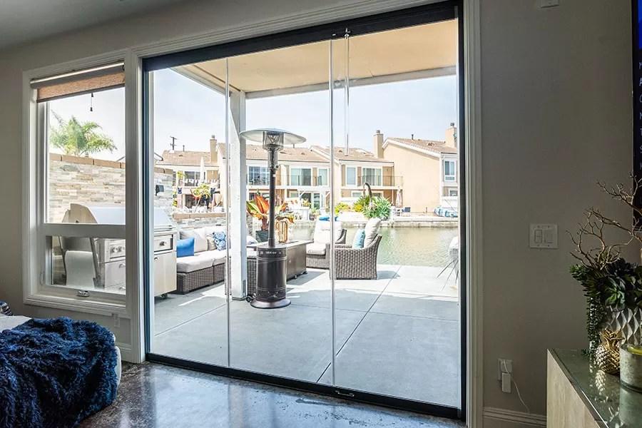 Looking at patio through enclosed frameless sliding glass doors.