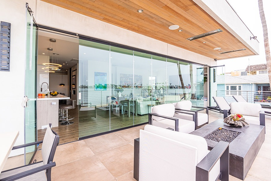 Patio with fire place and frameless glass doors enclosed with doors opened on each end.