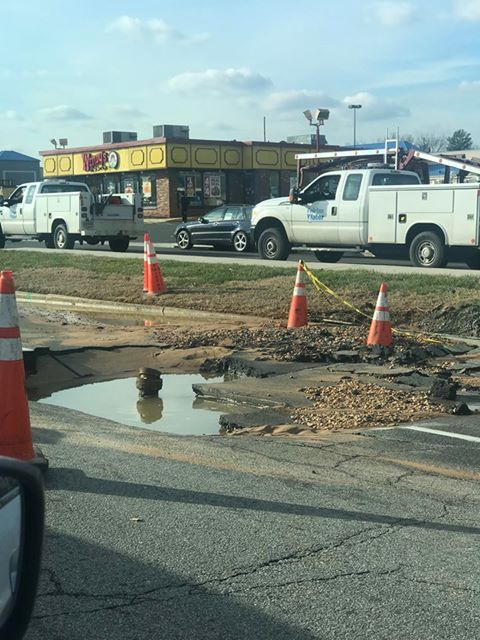 Broken ground with puddle on road