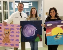 Student, doctor and another employee holding image