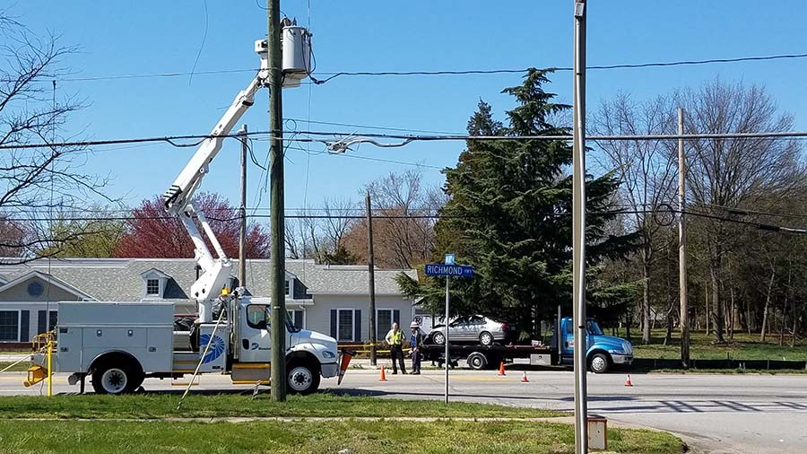 Dominion bucket truck working with tow truck hauling car away next to it.