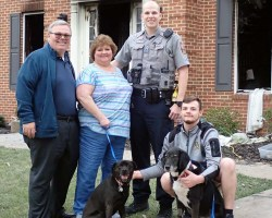 Family standing with two dogs, officer
