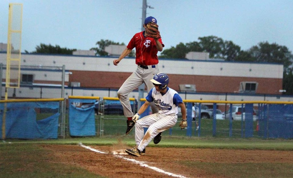 TC player in the air to make a catch as West Po player stands on third base