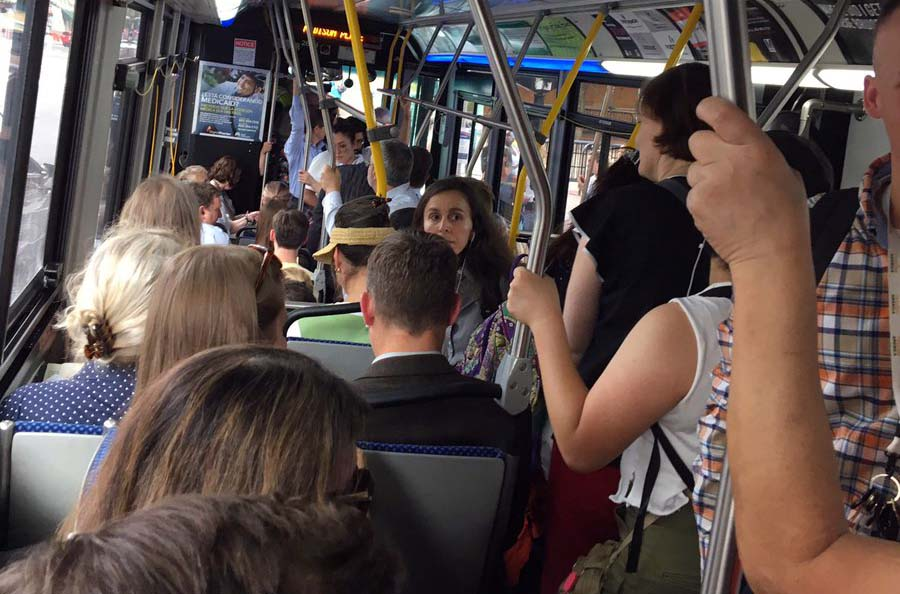 People crowded onto bus, standing in aisles