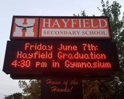 Sign in front of school with graduation information on it