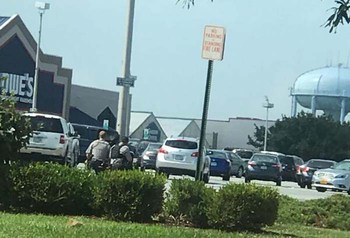 Lowe's in background of image with police kneeling in foreground
