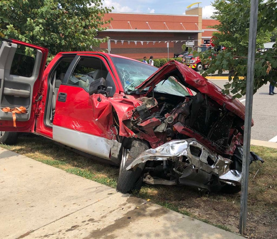 Red truck in crash, smashed in the front section